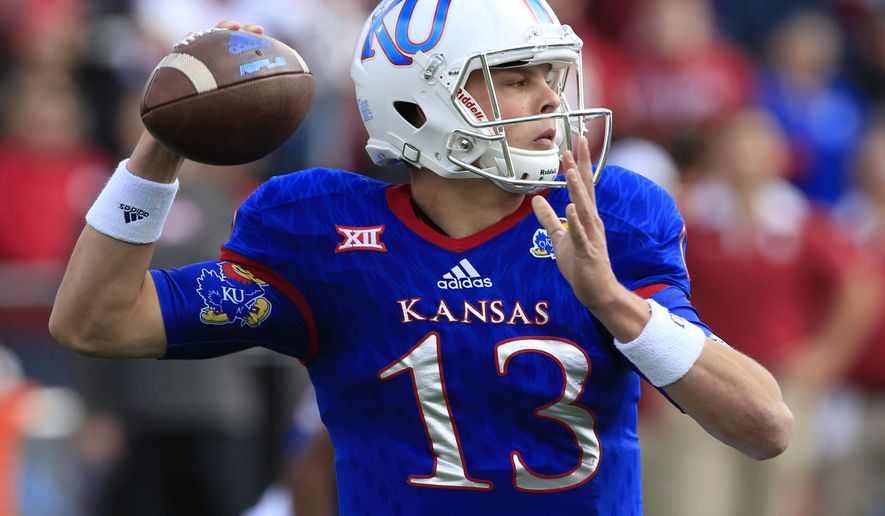 Kansas quarterback Ryan Willis (13) passes to a teammate during the first half of an NCAA college football game against Oklahoma in Lawrence, Kan., Saturday, Oct. 31, 2015. (AP Photo/Orlin Wagner)