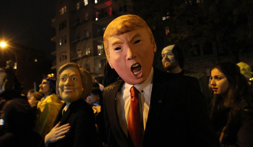 David Jiang, wearing a Donald Trump mask, and his girlfriend Kaja Klupinska, wearing a Hillary Clinton mask, left, make their way up Sixth Avenue during the Greenwich Village Halloween Parade, Saturday Oct. 31, 2015, in New York.  (AP Photo/Tina Fineberg)