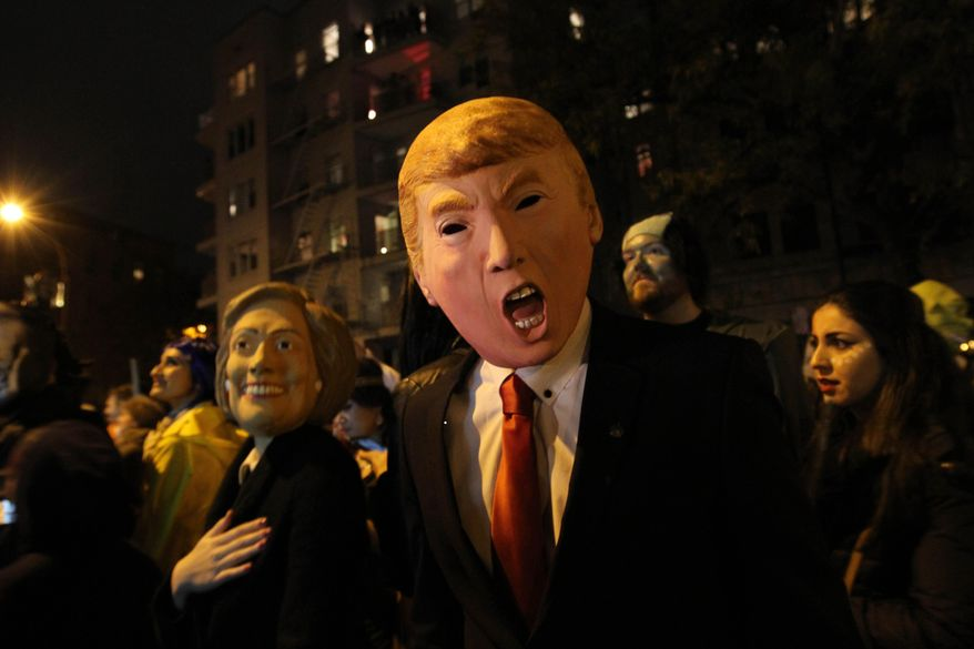 David Jiang, wearing a Donald Trump mask, and his girlfriend Kaja Klupinska, wearing a Hillary Clinton mask, left, make their way up Sixth Avenue during the Greenwich Village Halloween Parade, Saturday Oct. 31, 2015, in New York.  (AP Photo/Tina Fineberg)