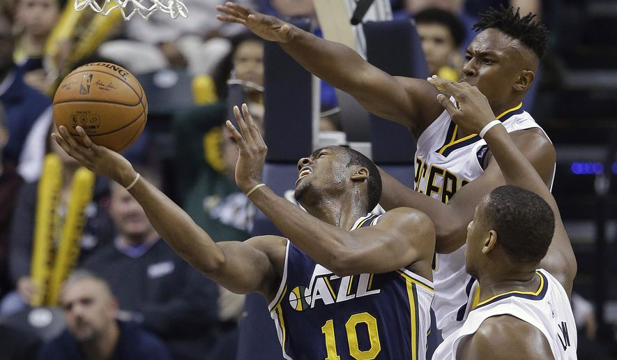 Utah Jazz's Alec Burks (10) shoots against Indiana Pacers' Myles Turner, top right, and Lavoy Allen, bottom right, during the first half of an NBA basketball game Saturday, Oct. 31, 2015, in Indianapolis. (AP Photo/Darron Cummings)