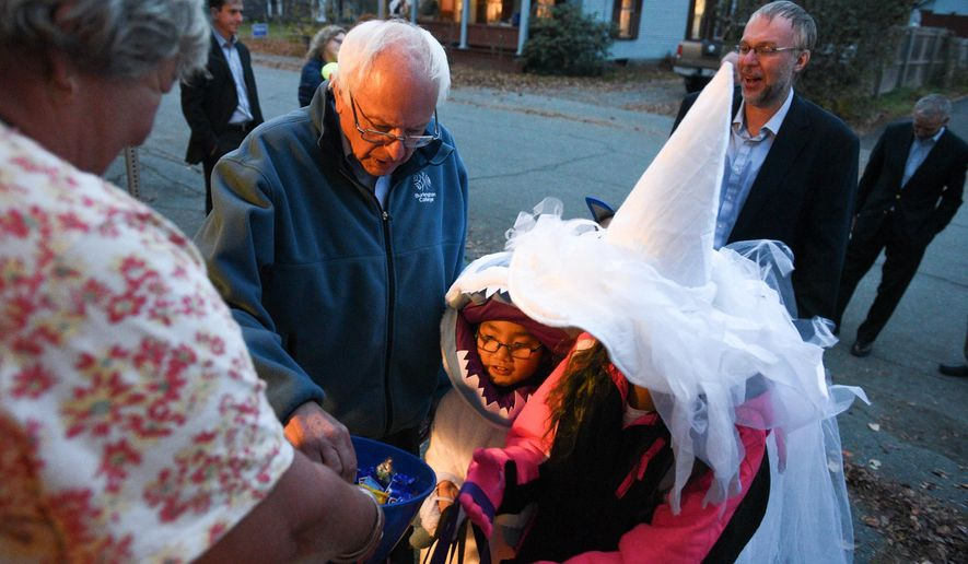 Barbara Teeter, left, holds a bowl of candy as Democratic presidential candidate Bernie Sanders, second from left, trick-or-treats with his grandchildren Grayson Riggs-Sanders, center, and Sunnee Riggs-Sanders, right, in Lebanon, N.H., Saturday, Oct. 31, 2015. (James M. Patterson/The Valley News via AP) MANDATORY CREDIT