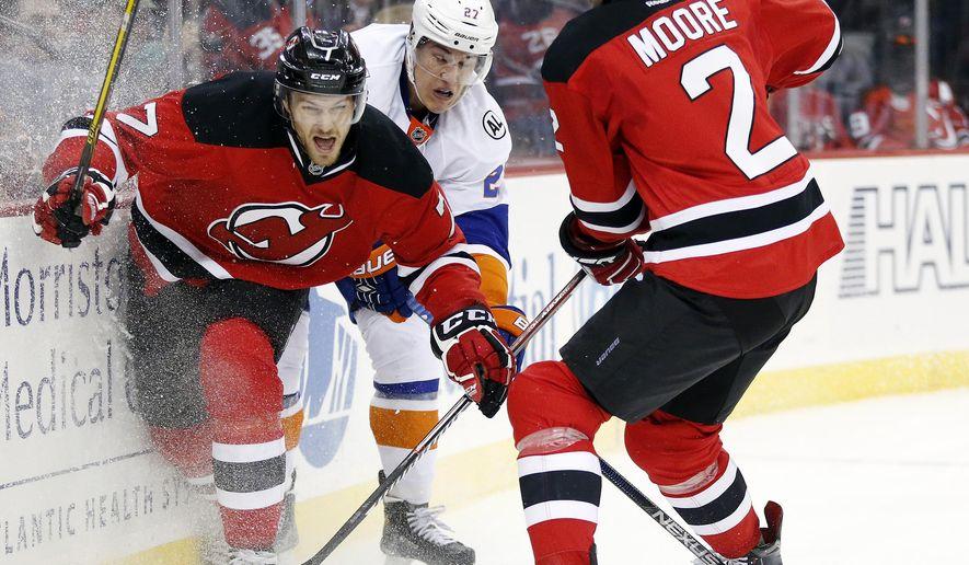 New York Islanders center Anders Lee, center, skates against New Jersey Devils defenseman Jon Merrill (7) and defenseman John Moore (2) during the first period of an NHL hockey game, Saturday, Oct. 31, 2015, in Newark, N.J. (AP Photo/Julio Cortez)
