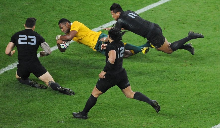 Australia's Tevita Kuridrani scores a try in the tackle of New Zealand's Julian Savea and New Zealand's Sonny Bill Williams during their Rugby World Cup final match between New Zealand and Australia at Twickenham Stadium, London, Saturday, Oct. 31, 2015. (AP Photo/Rob Taggart)