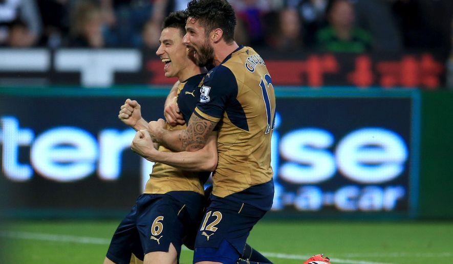 Arsenal's Laurent Koscielny celebrates scoring his side's second goal of the game with teammate Olivier Giroud, right, during their English Premier League soccer match against Swansea at the Liberty Stadium, Swansea, Wales, Saturday, Oct. 31, 2015. (Nick Potts/PA via AP)      UNITED KINGDOM OUT     -     NO SALES     -     NO ARCHIVES