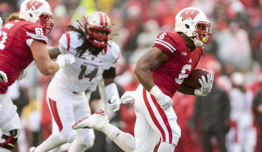 Wisconsin running back Corey Clement (6) runs for a touchdown as Wisconsin offensive lineman Tyler Marz (61) defends against Rutgers Kaiwan Lewis (14) during the first half of an NCAA college football game Saturday, Oct. 31, 2015, in Madison, Wis. (AP Photo/Andy Manis)