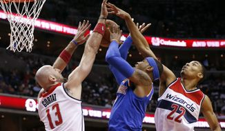 New York Knicks forward Carmelo Anthony, center,shoots between Washington Wizards center Marcin Gortat (13), from Poland, and forward Otto Porter Jr. (22) in the first half of an NBA basketball game, Saturday, Oct. 31, 2015, in Washington. (AP Photo/Alex Brandon)
