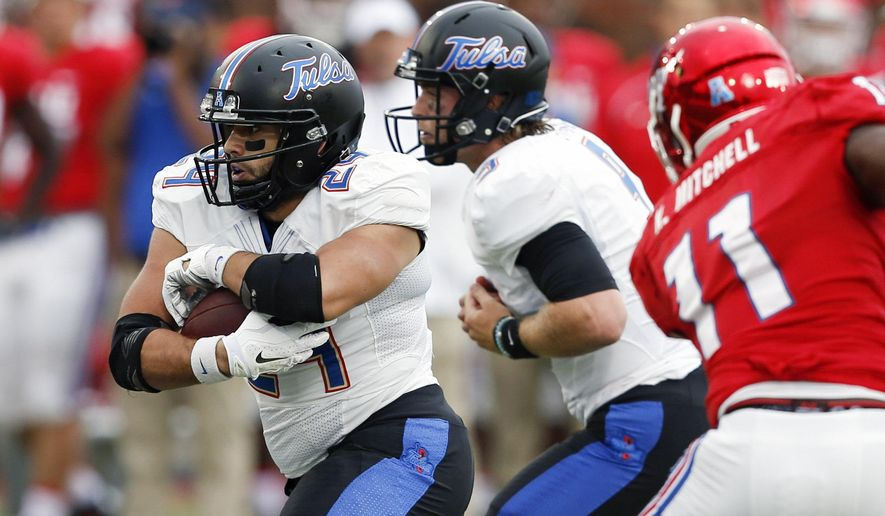Tulsa running back Zack Langer (24) runs after a handoff from Dane Evans against SMU during the first half of an NCAA college football game, Saturday, Oct. 31, 2015, in Dallas. (AP Photo/Jim Cowsert)