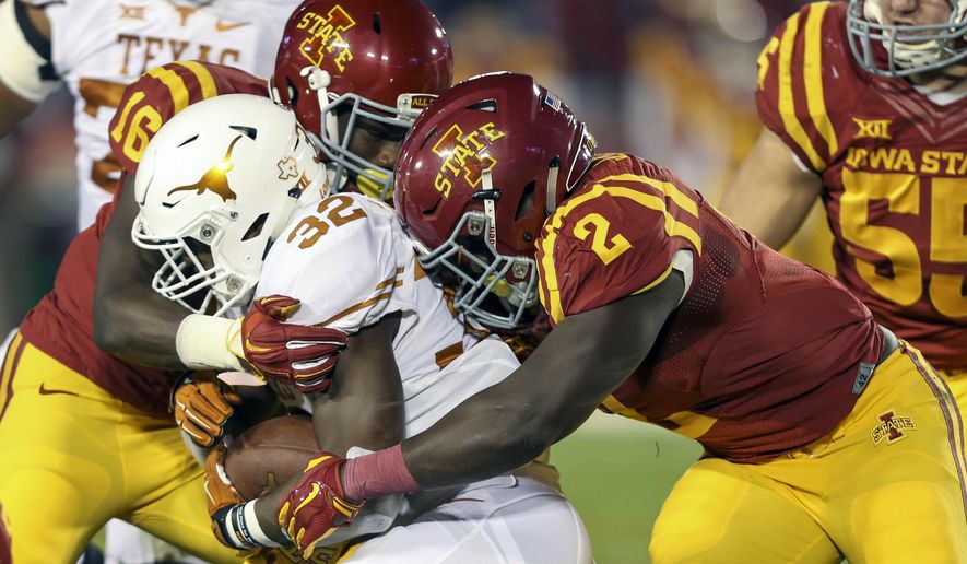 Iowa State linebacker Willie Harvey and Iowa State linebacker Jordan Harris wrap up Texas running back Johnathan Gray during the first half of an NCAA college football game, Saturday, Oct. 31, 2015, in Ames, Iowa. (AP Photo/Justin Hayworth)