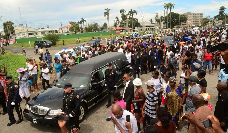 New York Police pall bearers walk alongside the hearse for Officer Randolph Holder during his funeral procession in Georgetown, Guyana, Saturday, Oct. 31, 2015. Holder was killed in New York city on Oct. 20 while responding to a report of shots fired and a bicycle stolen at gunpoint in Manhattan's East Harlem neighborhood. (AP Photo/Adrian Narine)