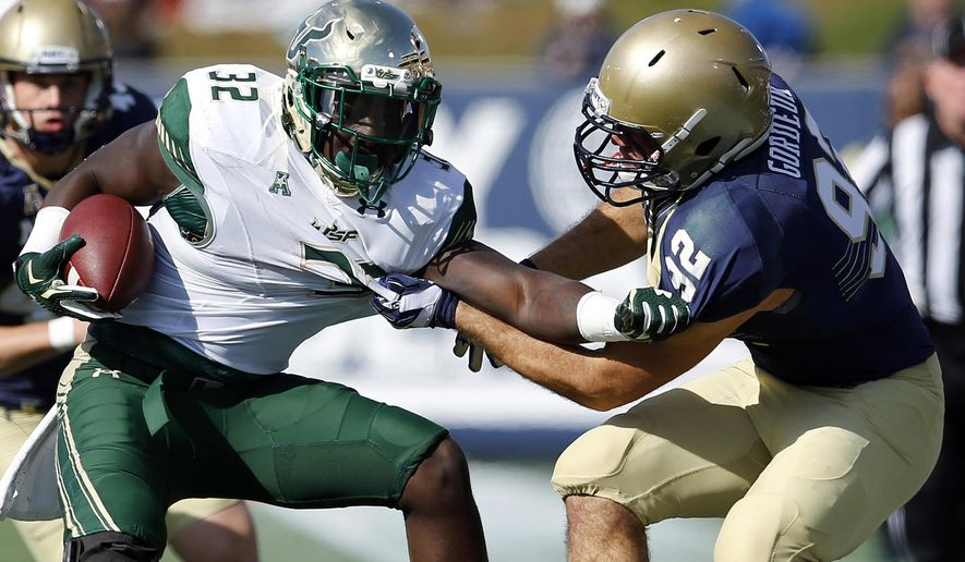 South Florida running back D'Ernest Johnson, left, tries to break free from Navy defensive end David Gordeuk as he rushes the ball in the first half of an NCAA college football game, Saturday, Oct. 31, 2015, in Annapolis, Md. (AP Photo/Patrick Semansky)