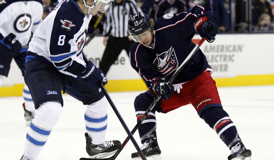 Columbus Blue Jackets' Cam Atkinson, right, works for the puck against Winnipeg Jets' Jacob Trouba during the second period of an NHL hockey game in Columbus, Ohio, Saturday, Oct. 31, 2015. (AP Photo/Paul Vernon)