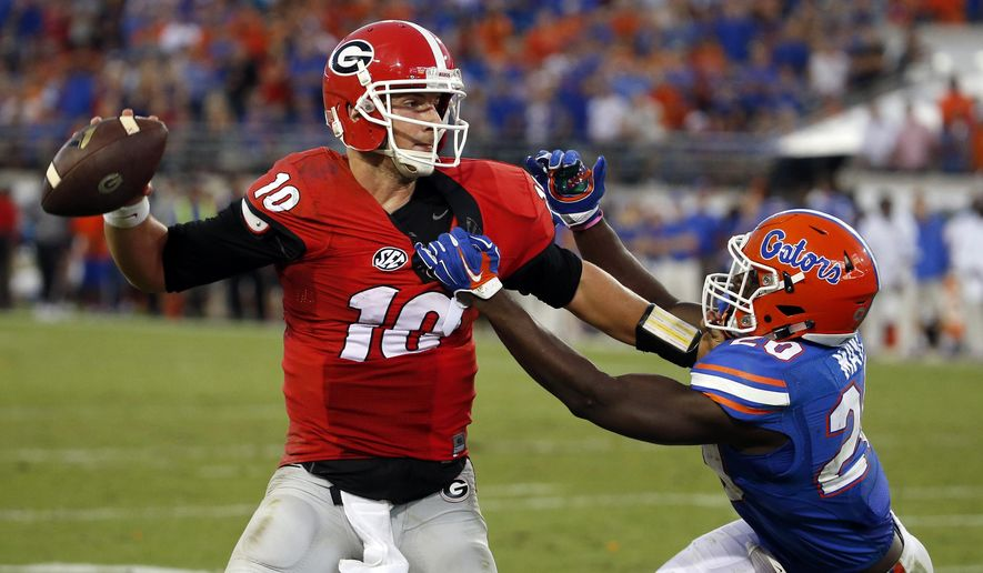 Georgia quarterback Faton Bauta (10) is pressured by Florida defensive back Marcus Maye (20) during the second half of an NCAA college football game, Saturday, Oct. 31, 2015, in Jacksonville, Fla. Bauta was intercepted in the end zone on the play. Florida defeated Georgia 27-3. (AP Photo/Stephen B. Morton)
