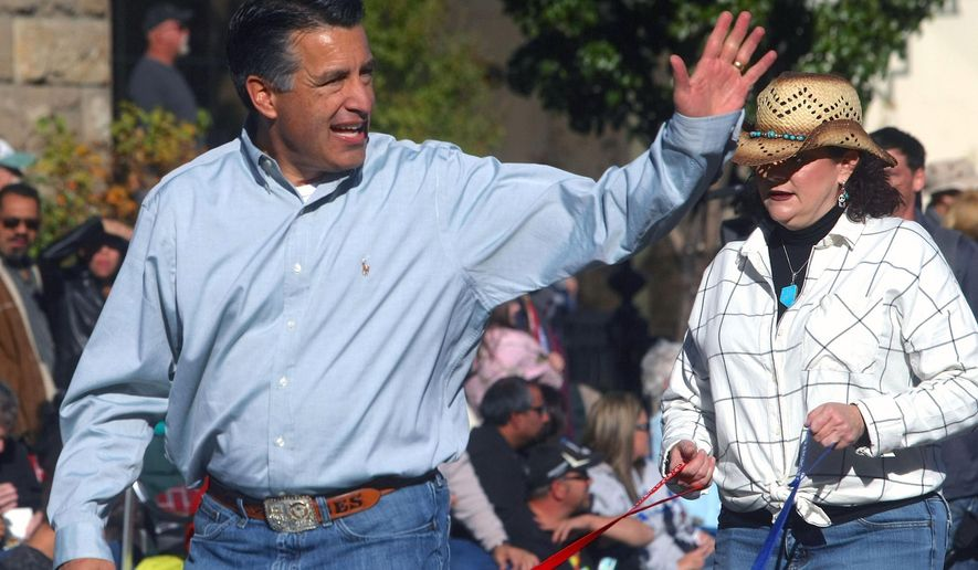 Nevada Gov. Brian Sandoval walks with his family during the Nevada Day Parade downtown Carson City, Nev., Saturday, Oct. 31, 2015. (Jim Grant/Nevada Appeal via AP) RENO GAZETTE-JOURNAL OUT