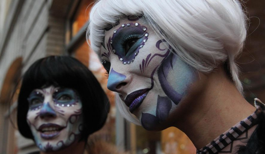 Angele Blank, right, and Virginia Promeyrat wait for the start of the Greenwich Village Halloween Parade, Saturday, Oct. 31, 2015 in New York. (AP Photo/Tina Fineberg)
