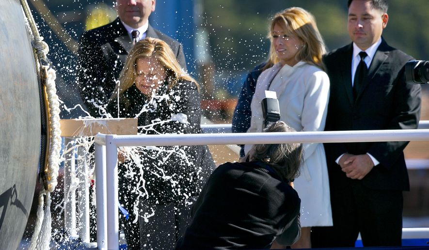 Rosa Peralta smashes a bottle of champagne to christen the USS Raphael Peralta, the 35th Arleigh Burke Class Missile Destroyer to be built by Bath Iron Works, Saturday, Oct. 31, 2015, in Bath, Maine. The warship is named for Rosa Peralta's son, Sgt. Raphael Peralta, who was killed in action on Nov. 15, 2004, while clearing houses in the city of Fallujah, Iraq, during Operation Al Fajr. Frederick J. Harris, president of General Dynamics Bath Iron Works, at left, and Rosa Peralta's daughter, Icela Peralta Donald, center, and son, Ricardo Peralta, join her on the platform.(AP Photo/Robert F. Bukaty)
