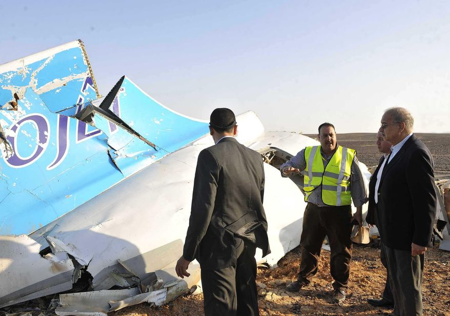 CORRECTS DAY OF WEEK TO SATURDAY, NOT FRIDAY - In this photo released by the Prime Minister's office, Sherif Ismail, right, looks at the remains of a crashed passenger jet in Hassana, Egypt on Saturday, Oct. 31, 2015. The Russian aircraft carrying 224 people crashed Saturday in a remote mountainous region in the Sinai Peninsula about 20 minutes after taking off from a Red Sea resort popular with Russian tourists, the Egyptian government said. There were no survivors. (Suliman el-Oteify/Egyptian Prime Minister's Office via AP)