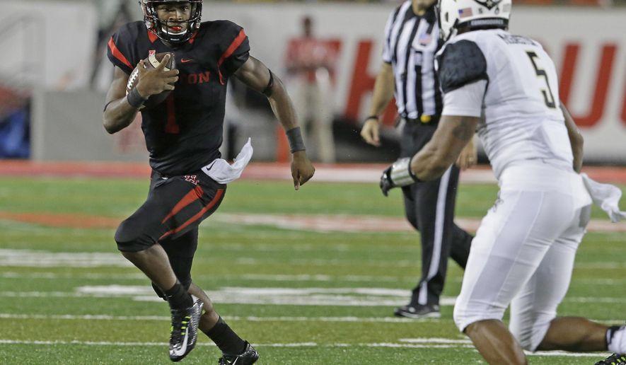 Houston  quarterback Greg Ward Jr. scrambles away from Vanderbilt's Torren McGaster (5) during the second half of an NCAA college football game Saturday, Oct. 31, 2015, in Houston. Houston won 34-0. (AP Photo/Pat Sullivan)