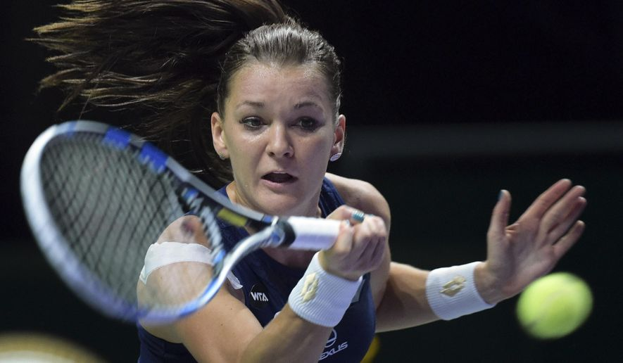 Agnieszka Radwanska of Poland makes a forehand return against Petra Kvitova of Czech Republic during the singles final at the WTA tennis finals in Singapore Sunday, Nov. 1, 2015. (AP Photo/Joseph Nair)