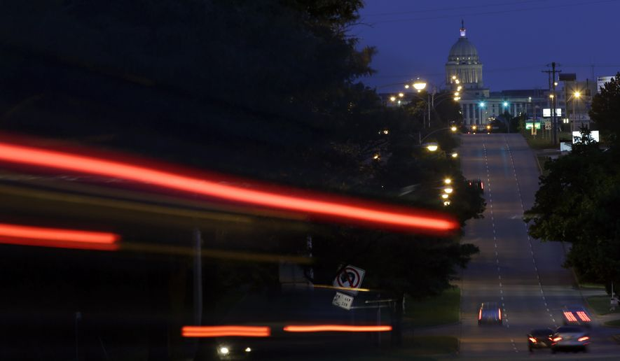 In this long exposure photo, cars travel along Lincoln Boulevard in Oklahoma City on Wednesday, June 10, 2015, near the site where a woman says she was sexually assaulted by Oklahoma City police officer Daniel Holtzclaw. Holtzclaw is accused of sexually assaulting 13 women he encountered while on patrol in neighborhoods near the state Capitol. (AP Photo/Eric Gay)