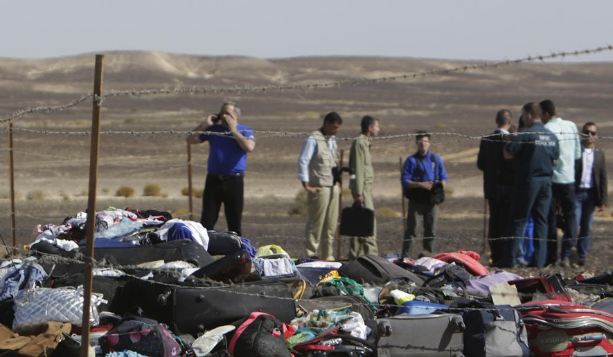 Russian investigators stand near debris, luggage and personal effects of passengers a day after a passenger jet bound for St. Petersburg in Russia crashed in Hassana, Egypt, on Sunday, Nov. 1, 2015. The Metrojet plane crashed 23 minutes after it took off from Egypt's Red Sea resort of Sharm el-Sheikh on Saturday morning. The 224 people on board, all Russian except for four Ukrainians and one Belarusian, died. (AP Photo/Amr Nabil)