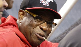 FILE - This Sept. 30, 2013 file photo, Cincinnati Reds manager Dusty Baker talks with visitors behind the batting cage during the baseball team's workout in Pittsburgh. The Reds decided to replace Baker on Friday, Oct. 4, 2013. (AP Photo/Gene J. Puskar)