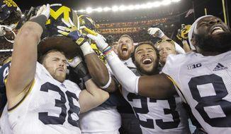 Michigan's Joe Kerridge (36), Jordan Glasgow (23) and A.J. Williams (84) carry the Little Brown Jug off the field after beating Minnesota 29-26 in an NCAA college football game Saturday, Oct. 31, 2015, in Minneapolis.(AP Photo/Paul Battaglia)