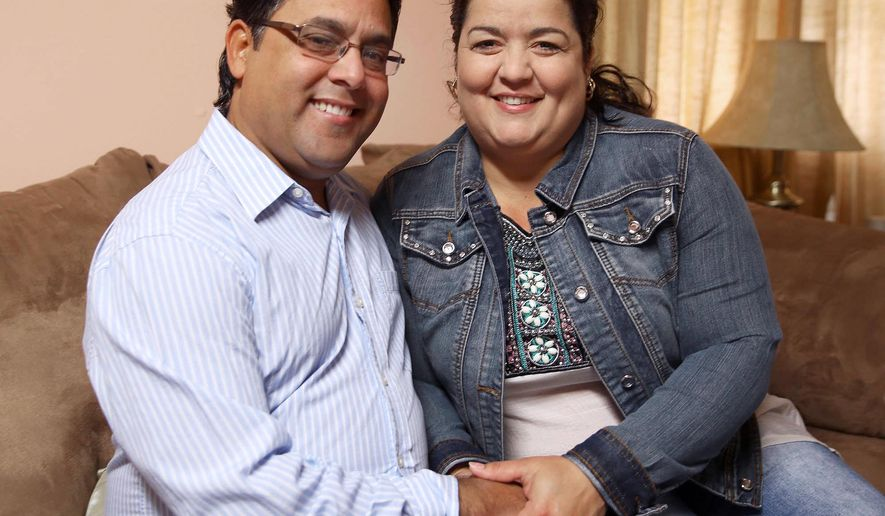 ADVANCE FOR USE SUNDAY, NOV. 1 -  In this photo taken Sept. 19, 2015, Esperanza Sosa Valdes and Ariel Del Sol Perez hold hands together as they pose in the living room of their home in Hastings, Neb. The couple navigated, negotiated, perspired and bribed their way along the perilous, 3,300-mile trek from Ecuador to the United States in the fall of 2012. It was a successful journey that landed them in Central Nebraska with enough stories to fill several books.  (Andrew Carpenean/The Independent via AP) MANDATORY CREDIT