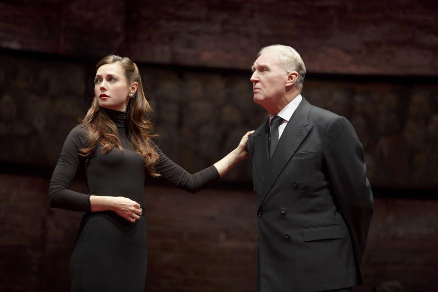 """This image released by The O + M Co. shows Lydia Wilson, left, and Tim Pigott-Smith during a performance of """"King Charles III,"""" at the Music Box Theatre in New York. Pigott-Smith stars in Mike Bartlett's """"King Charles III,"""" an ingenious view of what might happen when the Prince of Wales finally inherits the throne. It was the winner of the 2015 Olivier Award for Best New Play. (Joan Marcus/The O + M Co. via AP)"""
