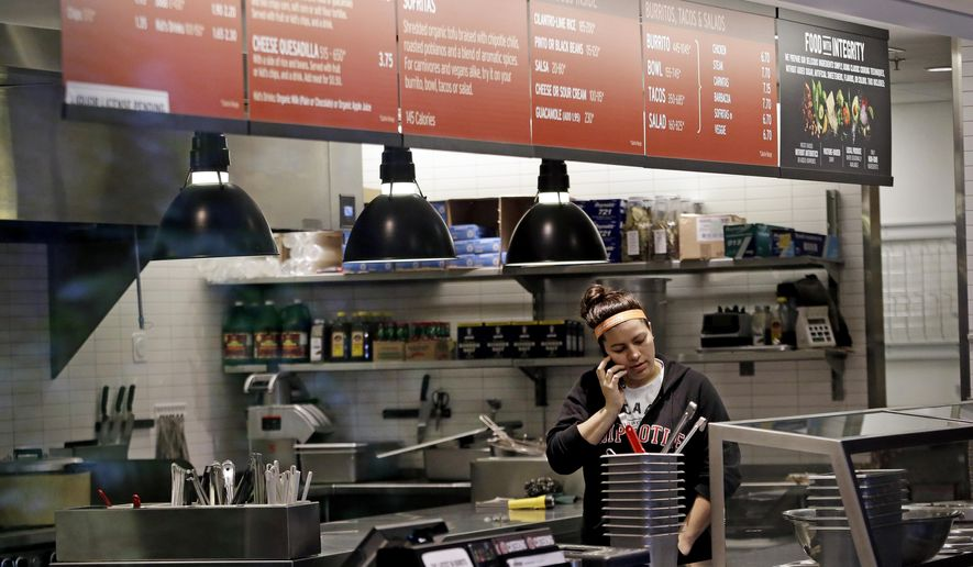 A woman talks on the phone as she stands in the kitchen area of a closed Chipotle restaurant, Monday, Nov. 2, 2015, in Seattle. An E. coli outbreak linked to Chipotle restaurants in Washington state and Oregon has sickened nearly two dozen people in the third outbreak of foodborne illness at the popular chain this year. Cases of the bacterial illness were traced to six of the fast-casual Mexican food restaurants, but the company voluntarily closed down 43 of its locations in the two states as a precaution. (AP Photo/Elaine Thompson)