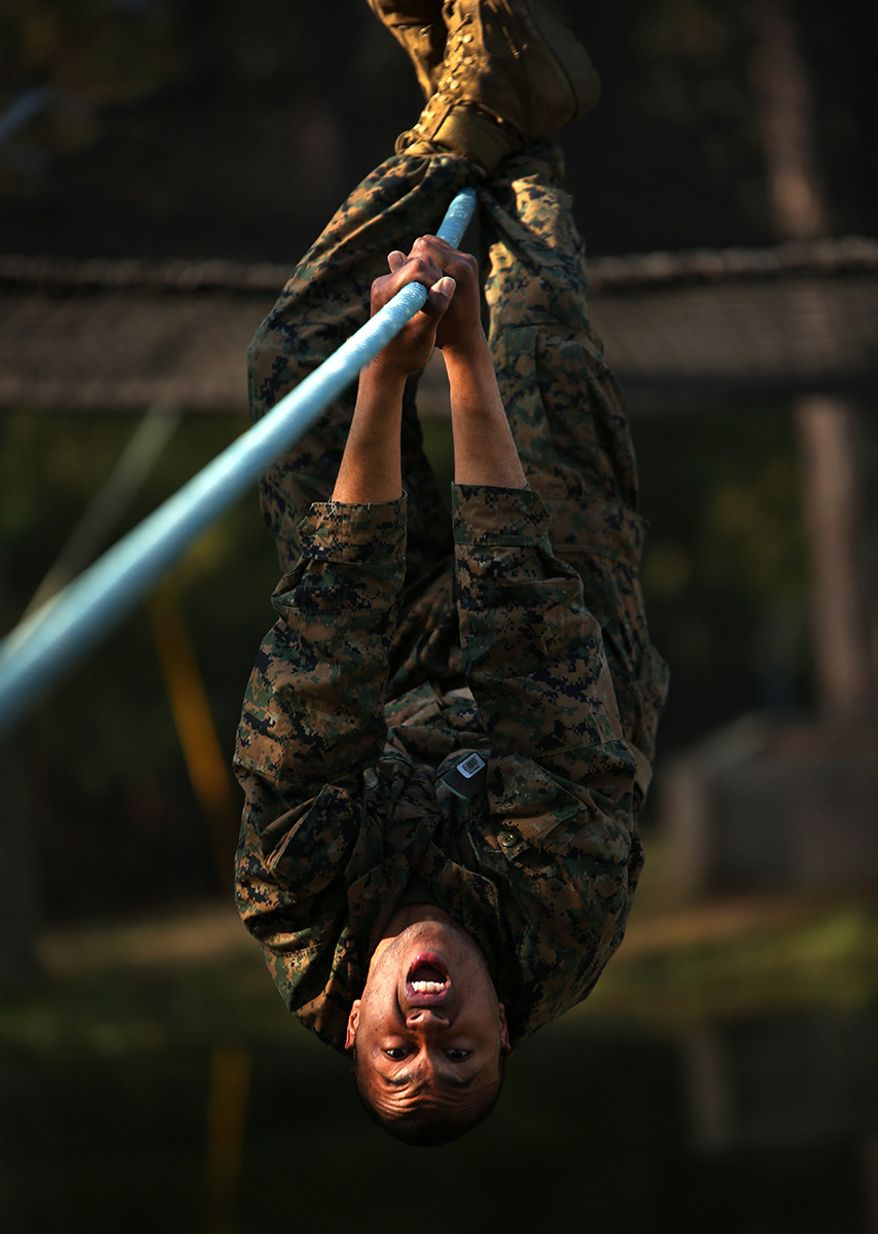Rct. Brock Willingham, Platoon 1024, Delta Company, 1st Recruit Training Battalion, responds to his drill instructor as he changes positions on a Confidence Course obstacle Feb. 25, 2014, on Marine Corps Recruit Depot Parris Island, S.C. For this obstacle, recruits had to change positions twice as they slid across a horizontal rope that hovered over a shallow pond. Willingham, a 22-year-old from Augusta, Ga., is scheduled to graduate May 2, 2014. Parris Island has been the site of Marine Corps recruit training since Nov. 1, 1915. Today, approximately 20,000 recruits come to Parris Island annually for the chance to become United States Marines by enduring 13 weeks of rigorous, transformative training.  (U.S. Marine Corps photo by Cpl. Octavia Davis/Released)