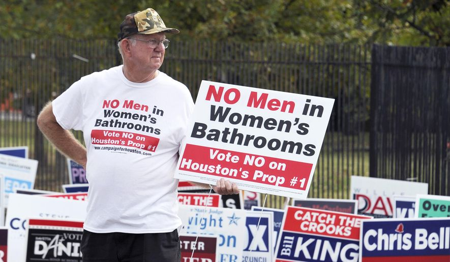In this Oct. 21, 2015 file photo, a man urges people to vote against the Houston Equal Rights Ordinance outside an early voting center in Houston. On Tuesday, Nov. 3, 2015, Houston voters repealed the nondiscrimination law. (AP Photo/Pat Sullivan, File)