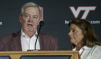 Virginia Tech NCAA college head football coach Frank Beamer, and his wife Cheryl Beamer, react during a press conference on the Virginia Tech campus in Blacksburg Va., Monday Nov. 2,  2015. Beamer has decided this will be his last season as Virginia Tech's coach, ending a 29-year run. (Matt Gentry/The Roanoke Times via AP)