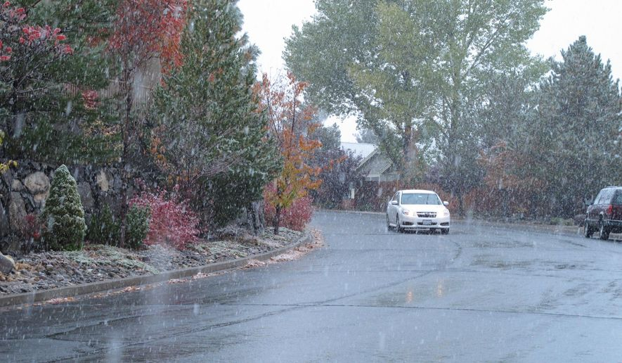 A car passes on a southwest Reno city street as snow begins to fall Monday, Nov. 2, 2015 in Reno, Nev. The first winter storm of the season was expected to drop more than a foot of snow in the upper elevations of the Sierra Nevada. (AP Photo/Scott Sonner)