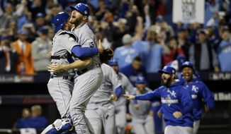 Kansas City Royals catcher Drew Butera and Wade Davis celebrate after Game 5 of the Major League Baseball World Series against the New York Mets Monday, Nov. 2, 2015, in New York. The Royals won 7-2 to win the series. (AP Photo/David J. Phillip)