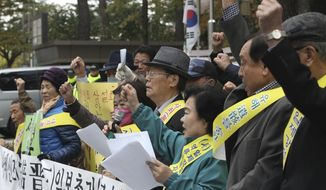 South Korean bereaved family members of victims of World War II stage a rally against Japanese Prime Minister Shinzo Abe's visit in front of the Japanese Embassy in Seoul, South Korea, Monday, Nov. 2, 2015. (AP Photo/Ahn Young-joon)