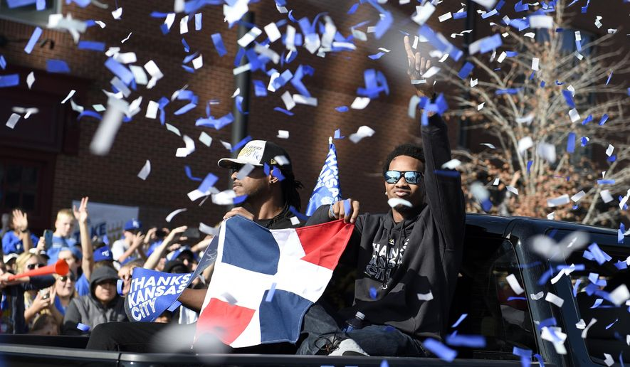 Kansas City Royals starting pitcher Yordano Ventura, right, holds a Dominican flag during a parade honoring the teams first baseball World Series trophy in 30 years. Tuesday, Nov. 3, 2015 in Kansas City.  (Shane Keyser /The Kansas City Star via AP) MANDATORY CREDIT