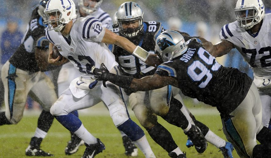 Indianapolis Colts' Andrew Luck (12) runs as Carolina Panthers' Kawann Short (99) defends in the first half of an NFL football game in Charlotte, N.C., Monday, Nov. 2, 2015. (AP Photo/Mike McCarn)