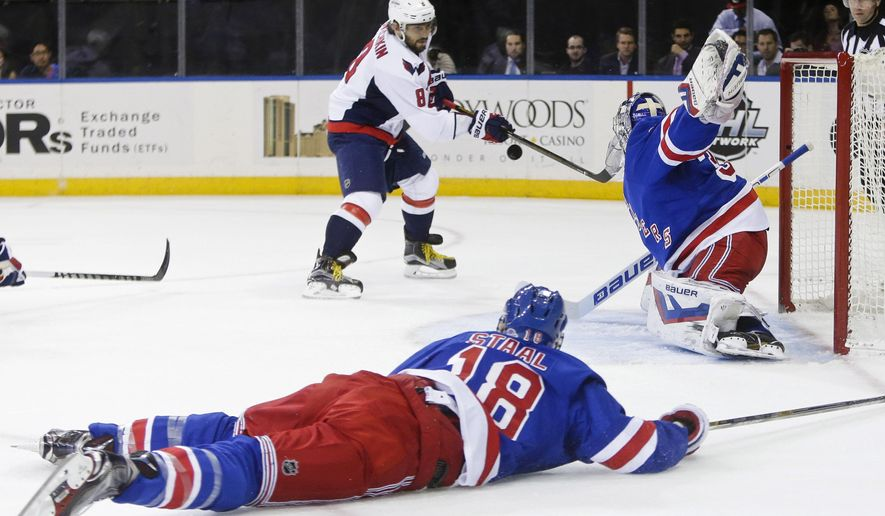 Washington Capitals' Alex Ovechkin (8), of Russia, shoots the puck past New York Rangers goalie Henrik Lundqvist (30), of Sweden, as Marc Staal (18) watches during the first period of an NHL hockey game Tuesday, Nov. 3, 2015, in New York. (AP Photo/Frank Franklin II)