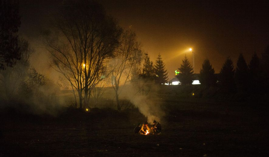Syrian refugees make a fire while waiting to be allowed to go into Austria at the Slovenian-Austrian border in Sentilj, Slovenia, Monday Oct. 2, 2015.  The influx of many hundreds of thousands of migrants into the European bloc over this year, is putting extreme pressure on local communities especially in border countries.  (AP Photo /Manu Brabo)