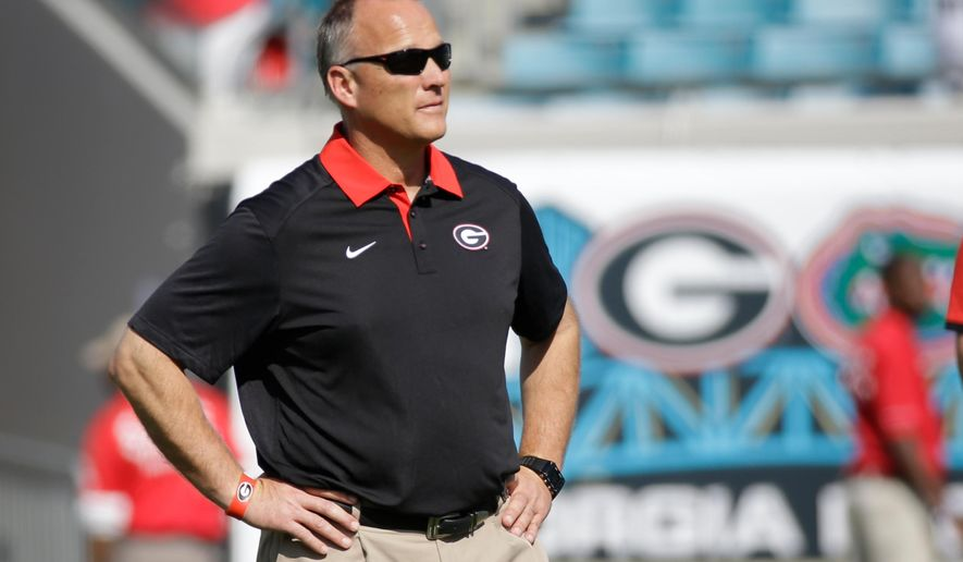 FILE - In this Oct. 31, 2015, file photo, Georgia head coach Mark Richt watches his team warm up before an NCAA college football game against Florida, in Jacksonville, Fla. Losses in three of four games, including last week's ugly loss at Florida, have turned up the heat on Georgia coach Mark Richt, whose challenge entering this week's game against Kentucky is made more difficult by a growing crisis at quarterback. (AP Photo/John Raoux, File)