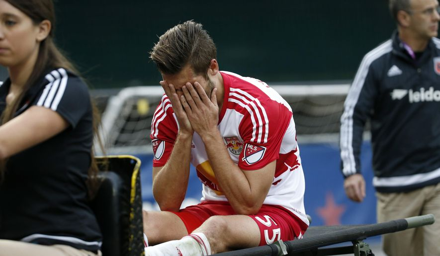 New York Red Bulls defender Damien Perrinelle (55) holds his face in his hands after he left the game with an injury during the second half of an MLS playoff soccer match against the D.C. United, at RFK Stadium, Sunday, Nov. 1, 2015, in Washington. New York won 1-0. (AP Photo/Alex Brandon)