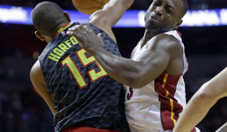 Miami Heat guard Dwyane Wade, right, collides with Atlanta Hawks forward Al Horford (15) during the first half of an NBA basketball game, Tuesday, Nov. 3, 2015, in Miami. (AP Photo/Alan Diaz)