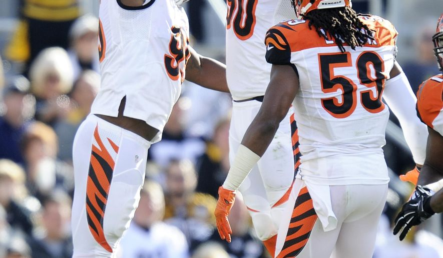 Cincinnati Bengals defensive ends Michael Johnson (90) and Wallace Gilberry (95) celebrate beside outside linebacker Emmanuel Lamur (59) after sacking Pittsburgh Steelers quarterback Ben Roethlisberger in the second quarter of an NFL football game Sunday, Nov. 1, 2015, in Pittsburgh. The Bengals won 16-10. (AP Photo/Don Wright)