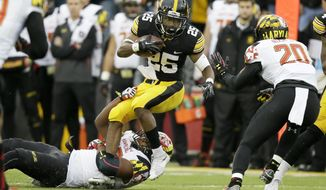 Iowa running back Akrum Wadley (25) tries to break a tackle by Maryland linebacker Jermaine Carter Jr., left, during the first half of an NCAA college football game, Saturday, Oct. 31, 2015, in Iowa City, Iowa. Iowa won 31-15. (AP Photo/Charlie Neibergall)