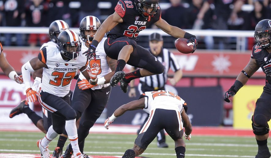 FILE - This Saturday, Oct. 31, 2015, file photo, shows Utah running back Devontae Booker (23) leaping over Oregon State cornerback Dwayne Williams (29) as teammate linebacker Jonathan Willis (32) pursues in the first quarter during an NCAA college football game  in Salt Lake City. Running backs Leonard Fournette and Dalvin Cook are regularly mentioned Heisman conversations.  Ezekiel Elliott and Royce Freeman are known commodities throughout college football. Booker, however, may be doing more with less than all of them for the No. 13 team in the country, and the Utes believe he's still underrated. (AP Photo/Rick Bowmer, File)