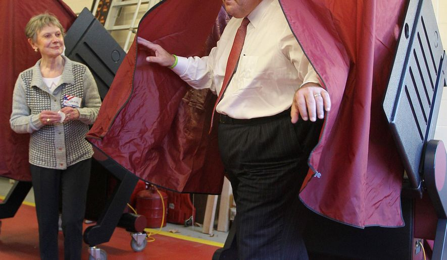 New Jersey Gov. Chris Christie emerges from the voting booth after voting Tuesday, Nov. 3, 2015, in Mendham Township, N.J. Looking on is Poll Worker Annie Barr. (AP Photo/Bill Denver)