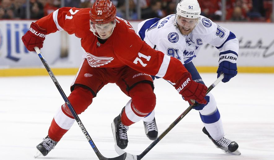 Detroit Red Wings center Dylan Larkin (71) and Tampa Bay Lightning center Steven Stamkos (91) skate for the puck during the second period of an NHL hockey game Tuesday, Nov. 3, 2015, in Detroit. (AP Photo/Paul Sancya)