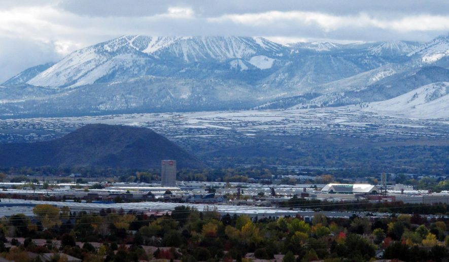 The Mount Rose Ski Resort, background, is covered in snow, Tuesday, Nov. 3, 2015, southwest of Reno, Nev.  The resort plans to open for the season on Nov. 4 after an early winter storm dumped more than a foot of snow on parts of the Sierra. (AP Photo/Scott Sonner).
