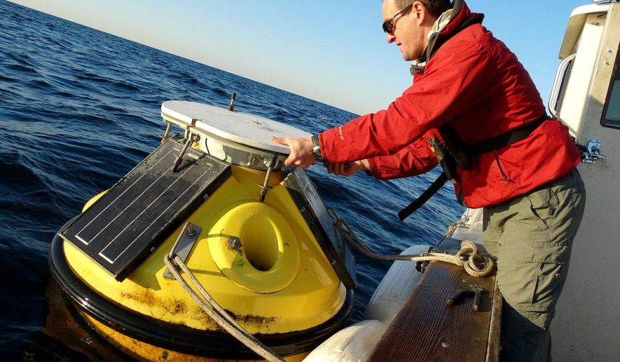 In this Oct. 26, 2015, photo, LimnoTech scientist Greg Cutrell removes a near-shore monitoring buoy from Lake Michigan. The high-tech buoy credited with supplying critical information about waves and weather on Lake Michigan might not return to the western Michigan coast next year unless money is found. (Garret Ellison/The Grand Rapids Press via AP) ALL LOCAL TELEVISION OUT; LOCAL TELEVISION INTERNET OUT; MANDATORY CREDIT