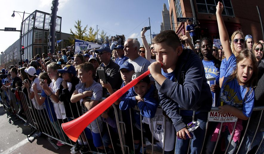 Fans cheer as a player is driven by during a parade celebrating the Kansas City Royals winning baseball's World Series Tuesday, Nov. 3, 2015, in Kansas City, Mo. The Royals beat the New York Mets in five games to win the championship. (A (AP Photo/Charlie Riedel)